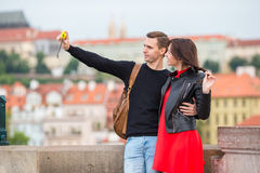 Young couple traveling on holidays in Europe smiling happy. Caucasian family making selfie in popular Karlov Most. Happy tourist couple, men and women traveling royalty free stock images