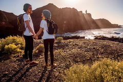 Young couple traveling nature. Young couple dressed alike with backpacks traveling island near the rocky ocean coast with lighthouse on the sunset stock image
