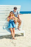 Young couple traveling, relaxing on the beach in New Jersey, USA. Modern Vacation. Wearing glasses, barefoot, dressing in summer outfits, girl and guy relying on Stock Image