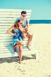 Young couple traveling, relaxing on the beach in New Jersey, USA. Modern Vacation. Wearing glasses, barefoot, dressing in summer outfits, girl and guy relying on Stock Images