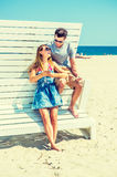 Young couple traveling, relaxing on the beach in New Jersey, USA. Modern Vacation. Wearing glasses, barefoot, dressing in summer outfits, girl and guy relying on Royalty Free Stock Photography