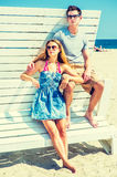 Young couple traveling, relaxing on the beach in New Jersey, USA. Young couple on the beach. Wearing glasses, barefoot, dressing in summer beach outfits, girl Royalty Free Stock Image