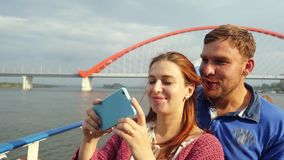 Young couple traveling by ship making selfie with mobile phone looking at shots on beautiful bridge background. Bright. Young couple traveling by ship making stock video