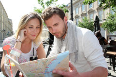 Young couple travelling in coffee shop looking at map Stock Photos