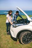 Young couple tries to fix the broken down car stock photo