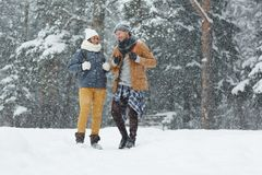 Young trippers. Young couple of trippers in winterwear enjoying their travel on snowy winter day Royalty Free Stock Images