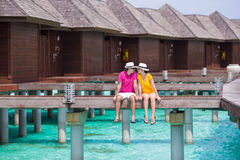 Young couple on tropical beach jetty near water Stock Images