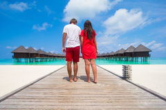 Young couple on tropical beach jetty at perfect Royalty Free Stock Photography