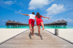 Young couple on tropical beach jetty at perfect Royalty Free Stock Image