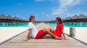Young couple on tropical beach jetty at perfect Royalty Free Stock Images