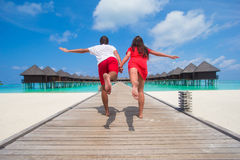 Young couple on tropical beach jetty at perfect Royalty Free Stock Photos