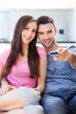 Young couple with TV remote Stock Image