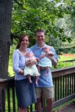 Young couple with twin babies. Happy young couple with twin babies in park, trees in background stock photo