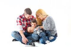 Young couple with two children. Young couple playing with their two children, sitting on the floor Stock Images
