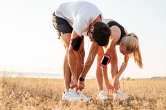 Young couple tying their shoes and getting ready for running. And working out together outdoors royalty free stock image