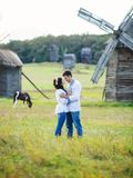 Young couple in Ukrainian shirts on the field. Young couple in Ukrainian traditional shirts on the field, old windmills in the background stock photo
