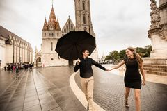 Young couple with umbrella walking in Budapest on a rainy day. Love story royalty free stock photography