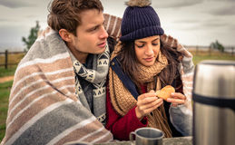 Young couple under blanket eating muffin outdoors Stock Photos