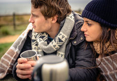 Young couple under blanket having hot drink in a Royalty Free Stock Photos