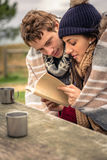 Young couple under blanket reading book outdoors Stock Image