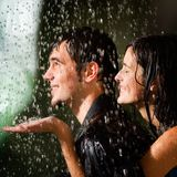 Young couple under a rain Stock Photos