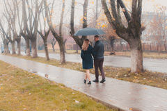 Young couple under an umbrella. Beautiful young couple walking under an umbrella in the autumn alley Stock Photo