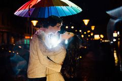 Young couple under an umbrella kisses at night on a city street. Lovers on a rainy date under a rainbow umbrella. Valentine`s Day Stock Images