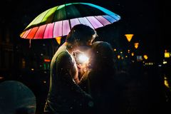 Young couple under an umbrella kisses at night on a city street. Lovers on a rainy date under a rainbow umbrella. Valentine`s Day Royalty Free Stock Photos