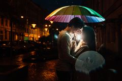 Young couple under an umbrella kisses at night on a city street. Lovers on a rainy date under a rainbow umbrella. Valentine`s Day Royalty Free Stock Photo