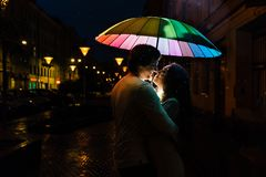 Young couple under an umbrella kisses at night on a city street. Lovers on a rainy date under a rainbow umbrella. Valentine`s Day Stock Image