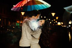 Young couple under an umbrella kisses at night on a city street. Lovers on a rainy date under a rainbow umbrella. Valentine`s Day Royalty Free Stock Image