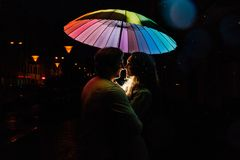 Young couple under an umbrella kisses at night on a city street. stock photo