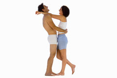 Young couple in underwear embracing, side view, cut out Stock Photos