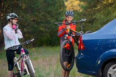 Young Couple Unmounting Mountain Bikes from Bike Rack on the Car. Adventure and Family Travel Concept. Stock Image