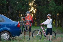 Young Couple Unmounting Mountain Bikes from Bike Rack on the Car. Adventure and Family Travel Concept. Stock Photos