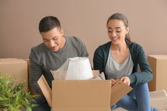 Young couple unpacking box indoors. Moving into new house stock photography