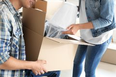 Young couple unpacking box indoors. Moving into new house royalty free stock photos