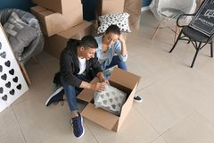 Young couple unpacking box indoors. Moving into new house stock photos