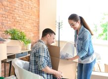 Young couple unpacking box indoors. Moving into new house stock images