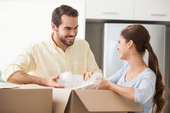 Young couple unpacking boxes in kitchen Stock Photos