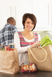 Young Couple Unpacking Shopping In Kitchen Royalty Free Stock Photo