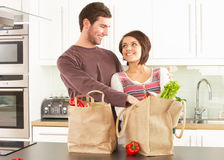 Young Couple Unpacking Shopping In Modern Kitchen Stock Images