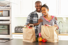 Young Couple Unpacking Shopping In Modern Kitchen royalty free stock photography