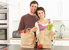 Young Couple Unpacking Shopping In Modern Kitchen Royalty Free Stock Photos