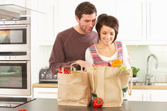 Young Couple Unpacking Shopping In Modern Kitchen Royalty Free Stock Image