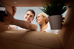 A young couple unpacks boxes. stock image