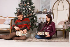 Young couple unwrapping their Christmas gifts Stock Photos