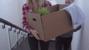 Young couple up the stairs with boxes in new house stock video footage