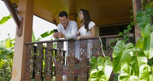 Young couple use cell smart phone talking stand on balcony in hotel, happy smiling man and woman surfing internet stock video footage