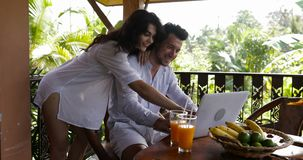 Young couple use laptop coputer together on terrace in summer forest, beautiful man and woman surfing internet talking stock video footage